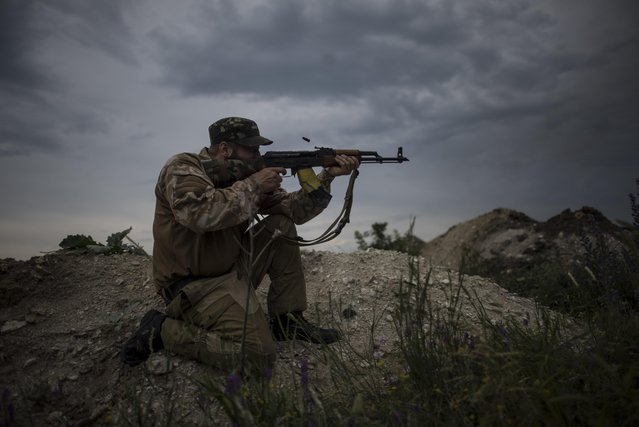 In this photo taken Tuesday, June 23, 2015, a Ukrainian serviceman from the Kiev-2 volunteer battalion fires his gun at a frontline in the village of Krymske, east Ukraine. (Photo by Evgeniy Maloletka/AP Photo)