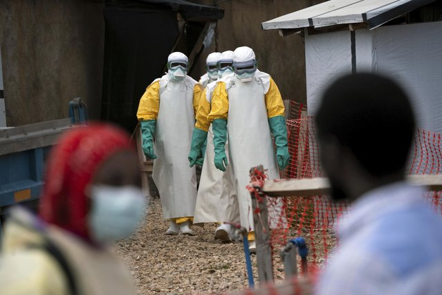 In this Tuesday, July 16, 2019 photo, health workers wearing protective gear begin their shift at an Ebola treatment center in Beni, Congo. On July 17, the World Health Organization declared the Ebola outbreak an international emergency after it spread to eastern Congo's biggest city, Goma. (Photo by Jerome Delay/AP Photo)
