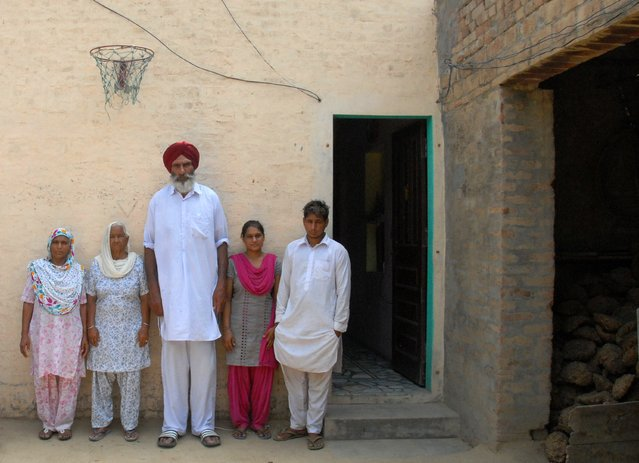 The family of newly drafted Indian NBA basketball player Satnam Singh (L/R): mother Sukhwinder Kaur, neighbour Kartar Kaur, father Balbir Singh Bhamara, sister Sarabjot Kaur and brother Beant Singh pose under a basketball hoop at his family home in the village of Ballo Ke, some 50kms south of Jalandhar on June 29, 2015. (Photo by Shammi Mehra/AFP Photo)