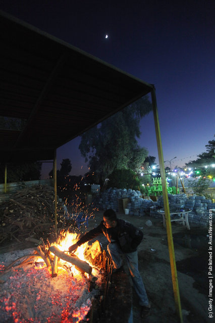 A worker prepares the traditional Iraqi fish dish Masgouf over a fire at an outdoor restaurant along the Tigris River