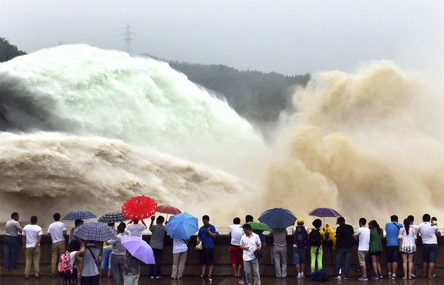 People look on as water gushes from the Xiaolangdi Reservoir section on the Yellow River, during a sand-washing operation in Jiyuan, Henan province, China, June 29, 2015. (Photo by Reuters/Stringer)