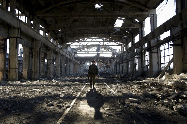"""An Ukrainian serviceman walks through the rubble of a destroyed workshop after fighting with pro-Russian separatists in Avdiivka, Donetsk region on March 31, 2017. US Secretary of State Rex Tillerson pressed NATO allies on March 31, 2017 to ramp up military spending and denounced Russia's """"aggression"""" in Ukraine, toughening the Trump administration's tone toward Moscow. (Photo by Anatolii Stepanov/AFP Photo)"""