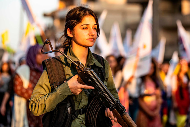 A member of the Kurdish Internal Security Police Force of Asayish stands guard as Syrian Kurdish demonstrate against Turkish threats to invade the Kurdish region, in the northeastern city of Qamishli on August 27, 2019. The Kurdish authorities in northeast Syria said Tuesday their forces had started to withdraw from outposts along the Turkish border after a US-Turkish deal for a buffer zone there. (Photo by Delil Souleiman/AFP Photo)