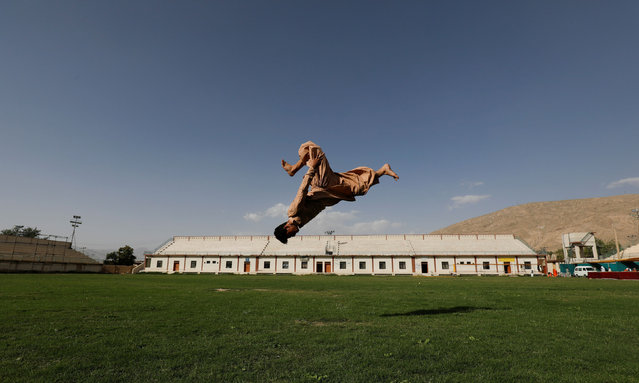 Syed Raza Hazara, 18, back flips as he performs Parkour at the Qayum Papa Stadium in Mariabad, Quetta, Pakistan, June 19, 2019. (Photo by Akhtar Soomro/Reuters)