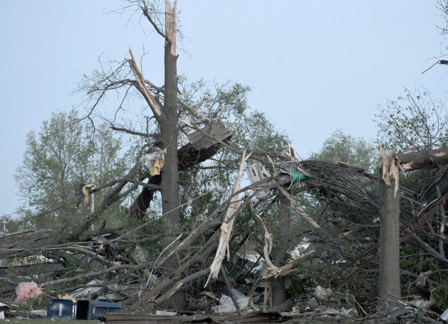Twisted trees and power lines remain in a residential block near Military Avenue following  the tornado in Baxter Springs, Kan., Sunday, April 27, 2014. A powerful storm system rumbled through the central and southern United States on Sunday, spawning a massive tornado that  carved through Little Rock's northern suburbs and another that hit Oklahoma and Kansas. (Photo by Roger Nomer/AP Photo/The Joplin Globe)