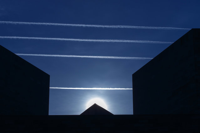 Contrails from jet planes passing overhead intersect the National Museum of Art in Washington, Thursday morning, April 17, 2014. (Photo by J. Scott Applewhite/AP Photo)