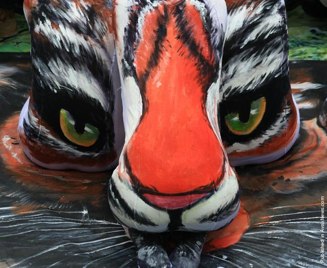 A tiger is painted on the backs of three models at the Three Lanes and Seven Alleys in Fuzhou, China