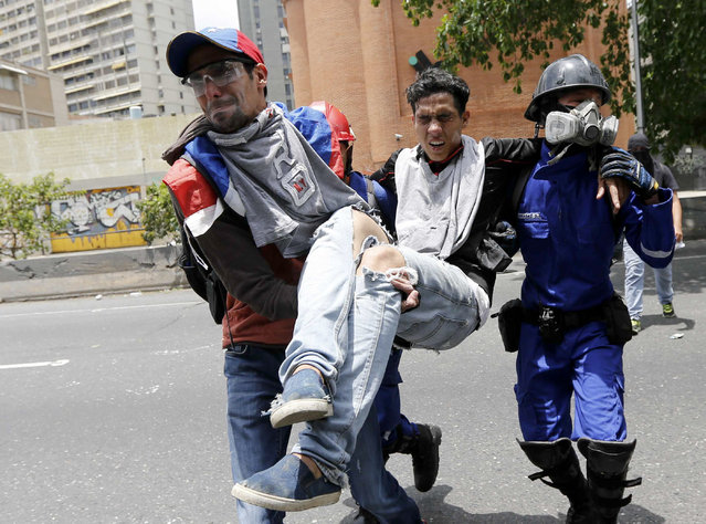 A protester is carried after being injured in clashes with security forces during anti-government protests in Caracas, Venezuela, Wednesday, April 19, 2017. (Photo by Ariana Cubillos/AP Photo)