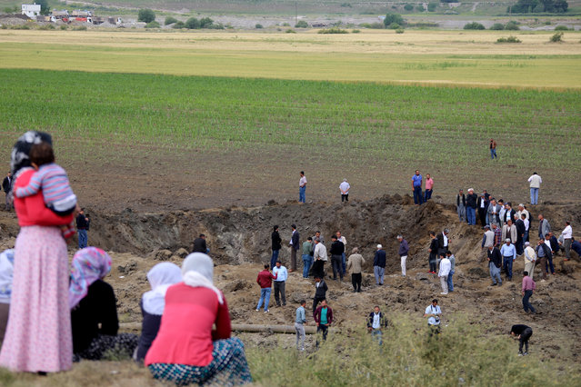 People gather at the site of last night's explosion near the Kurdish-dominated southeastern city of Diyarbakir, Turkey May 13, 2016. (Photo by Sertac Kayar/Reuters)