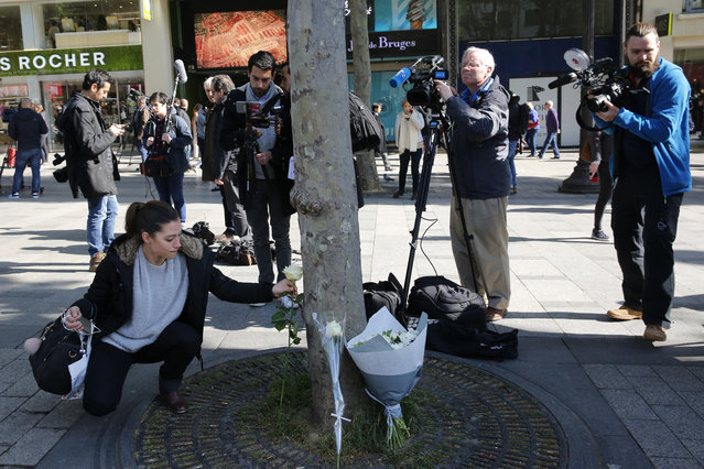 A woman lays a flower at the place of Thursday's attack on the Champs Elysees boulevard in Paris, Friday, April 21, 2017. France began picking itself up Friday from another deadly shooting claimed by the Islamic State group, with President Francois Hollande convening the government's security council and his would-be successors in the presidential election campaign treading carefully before voting this weekend. (Photo by Christophe Ena/AP Photo)