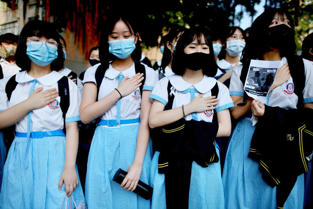 Schoolmates of form five student Tsang Chi-kin, 18, who was shot in the chest by police during violent pro-democracy protests that coincided with China's October 1 National Day, place their hands on their chests during a protest at a school in Hong Kong on October 2, 2019. Hundreds of Hong Kongers staged a sit-in on October 2 outside the school of a protester who was shot by police as authorities said the wounded 18-year-old was now in a stable condition. (Photo by Mohd Rasfan/AFP Photo)