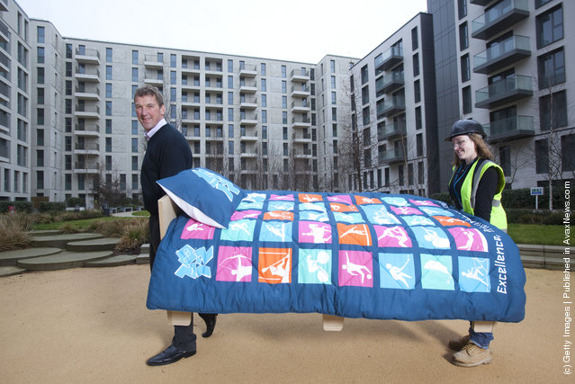 Olympian Matthew Pinsent helps lift in the first of 16,000 beds to be installed in Village as the ODA completes construction of apartments on time and LOCOG begins Games-time fit-out of Village