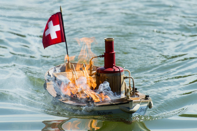 A steam-powered tugboat after it caught on fire during the NAVIGA NS World Championship for Scale Ship Models in Bankut, some 180 kms northeast of Budapest, Hungary, 12 July 2015. At the week-long event, 250 competitors attend with 320 ship models from 14 countries. (Photo by Peter Komka/EPA)