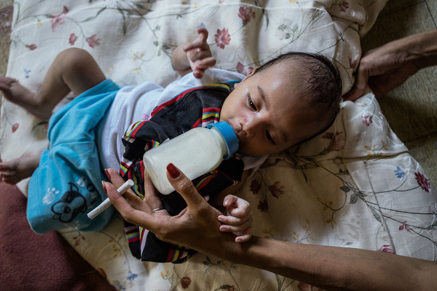 Jojo,  feeds her child in Angeles City. (Photo by Hannah Reyes Morales/The Washington Post)