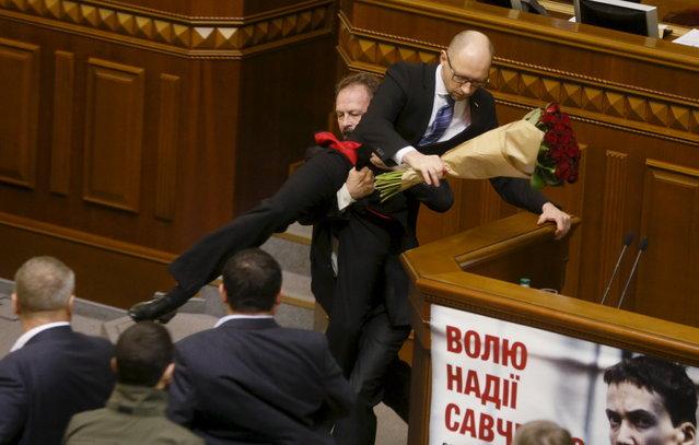 Rada deputy Oleg Barna removes Ukrainian Prime Minister Arseny Yatseniuk from the tribune, after presenting him a bouquet of roses, during the parliament session in Kiev, Ukraine, December 11, 2015. (Photo by Valentyn Ogirenko/Reuters)