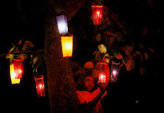 A boy hangs Vesak buckets on a tree, at a house, during the birth anniversary of Buddha, also known as Vesak Day, in Colombo, Sri Lanka May 10, 2017. (Photo by Dinuka Liyanawatte/Reuters)