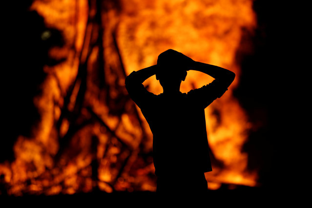 An Ultra-Orthodox Jewish boy stands around a bonfire as he celebrates the Jewish holiday of Lag Ba'Omer in the city of Ashdod, Israel May 25, 2016. (Photo by Amir Cohen/Reuters)