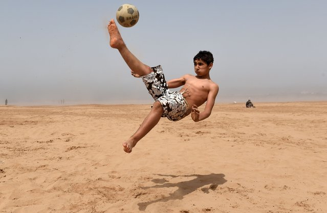 A boy controls a ball as he plays football on a beach in the western Moroccan city of Essaouira on June 13, 2014. (Photo by Fadel Senna/AFP Photo)