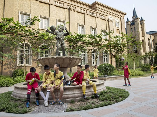 Young Chinese football players sit together in the campus as they wait to head to training at the Evergrande International Football School near Qingyuan in Guangdong Province. (Photo by Kevin Frayer/Getty Images)