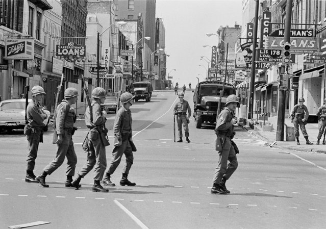 A relief squad of the Tennessee National Guard files across Beale Street in Memphis, Tenn., to replace troopers already stationed at strategic points in the racially tense city, March 30, 1968. The troops have been on duty in Memphis since violence erupted during a march led by Dr, Martin Luther King Jr. on March 28. (Photo by Charles Kelly/AP Photo)