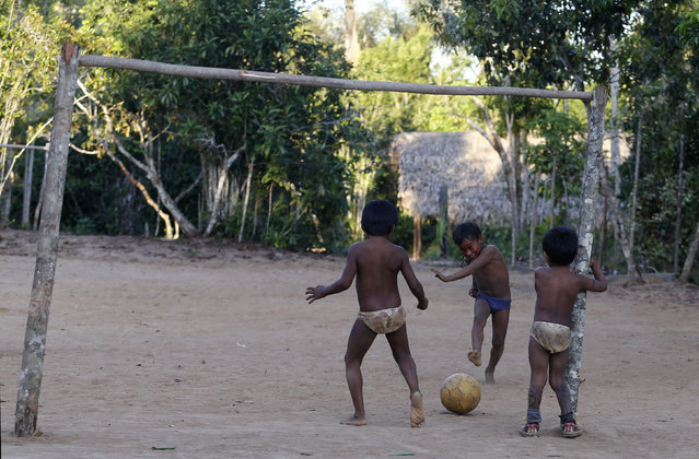Children of the Amazonian Tatuyo tribe play soccer in their village in the Rio Negro (Black River) near Manaus city, a World Cup host city, June 23, 2014. Because of their proximity to host city Manaus and their warm welcome, the Tatuyo have enjoyed three weeks of brisk business thanks to the World Cup. Usually, they host between 10 and 30 tourists a day. During the World Cup, this number has rocketed to 250 a day, They have become richer and other communities now come to them to sell them juices and fishes. (Photo by Andres Stapff/Reuters)