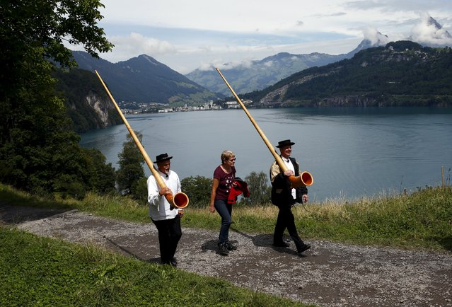 Spectators and alphorn blowers arrive for the Swiss national holiday celebrations on the Ruetli meadows in central Switzerland August 1, 2015. (Photo by Arnd Wiegmann/Reuters)
