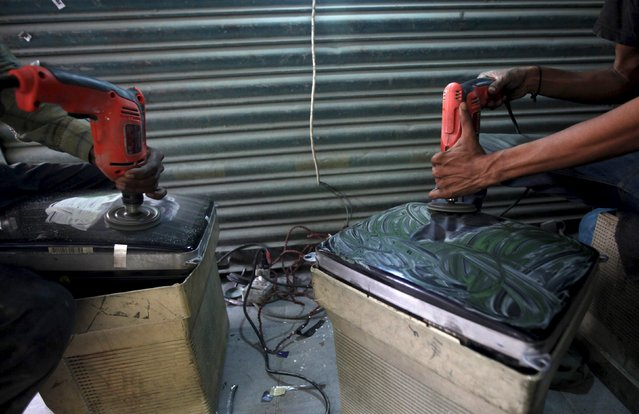 Workmen polish the screens of computer monitors to fit them into homemade television sets at a market in Karachi, Pakistan, July 29, 2015. (Photo by Akhtar Soomro/Reuters)