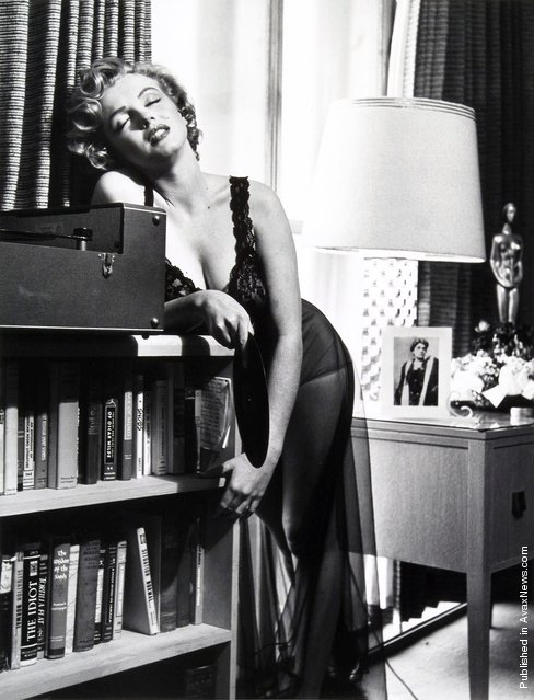 American actress, singer, model and showgirl Marilyn Monroe  posing in her two bedroom apartment. Under the lamp is a picture of Italian actress Eleonora Duse, whom Marilyn Monroe admired greatly. USA, Hollywood, California, 1952