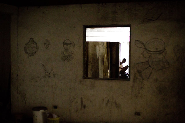 In this June 26, 2015 photo, single mother Manushka Doneis, 18, sits inside the abandoned shipping company building where she lives with her siblings and five-month-old daughter in Port-au-Prince, Haiti. Haitians who are homeless since the 2010 earthquake can be found living in the best conditions they can find – the ruins of a luxury hotel, makeshift shelters on the grounds of the destroyed national theater, and even in one case in an unventilated trailer. (Photo by Rebecca Blackwell/AP Photo)
