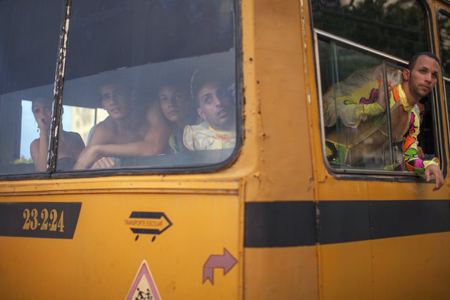 Revelers in a bus watch a fight taking place on a street before their performance at a carnival parade in Havana August 8, 2014. (Photo by Alexandre Meneghini/Reuters)