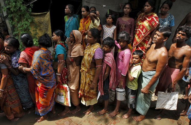 Flood-affected people stand in a queue as they wait for relief supplies at Howrah district in West Bengal, India, August 5, 2015. (Photo by Rupak De Chowdhuri/Reuters)