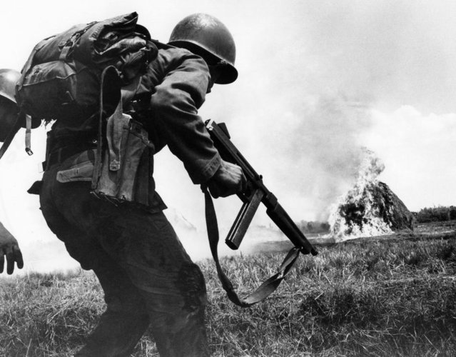 A Vietnamese infantryman jumps from the protection of a rice paddy dike for another short charge during a run and fire assault on Viet Cong Guerrillas entrenched in an area 15 miles west of Saigon on April 4, 1965