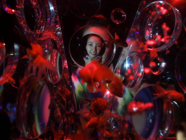 """A young Japanese woman dressed in yukata looks at goldfish swimming in the """"Reflectrium"""" installation as she poses during a press preview of the """"Art Aquarium"""" exhibition as part of the """"Eco Edo Nihonbashi 2014"""" summer event at Nihonbashi Mitsui Hall in Tokyo, Japan, 10 July 2014. Some 5,000 goldfish are on display with the various latest techniques at the art exhibition, which will be opened to the public between 11 July to 23 September. (Photo by Kiyoshi Ota/EPA)"""