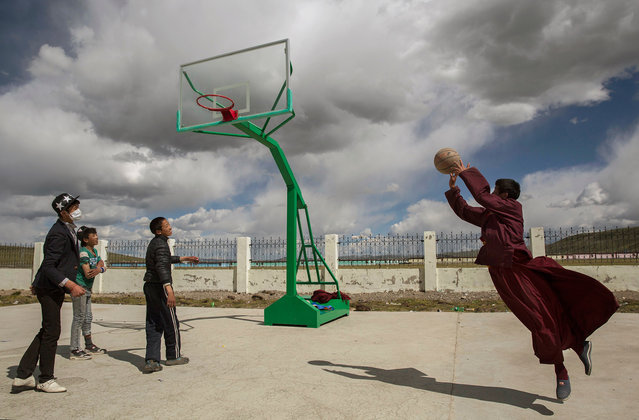 A Tibetan Buddhist monk leaps as he shoots a backet while playing basketball with friends at a school in  a government resettlement community for former nomads on July 23, 2015 on the Tibetan Plateau in Yushu County, Qinghai, China. (Photo by Kevin Frayer/Getty Images)