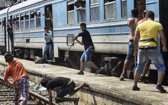 Migrants with a stick, stones and knife fight with each other after a brawl erupted over a place in an overcrowded train heading to the Serbian border at the train station in Gevgelija, The Former Yugoslav Republic of Macedonia, 14 August 2015. (Photo by Georgi Licovski/EPA)
