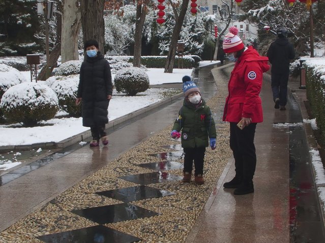 People wear face masks as they walk in public park on a snowy day in Beijing, Sunday, February 2, 2020. The Philippines on Sunday reported the first death from a new virus outside of China, where authorities delayed the opening of schools in the worst-hit province and tightened quarantine measures in a city that allow only one family member to venture out to buy supplies. (Photo by Miriam Saleh via AP Photo)
