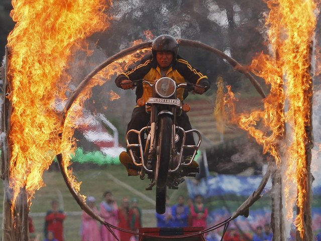 A Kashmiri policeman performs a stunt on a motorbike through a ring of fire during India's Independence Day celebrations in Srinagar, August 15, 2015. (Photo by Danish Ismail/Reuters)