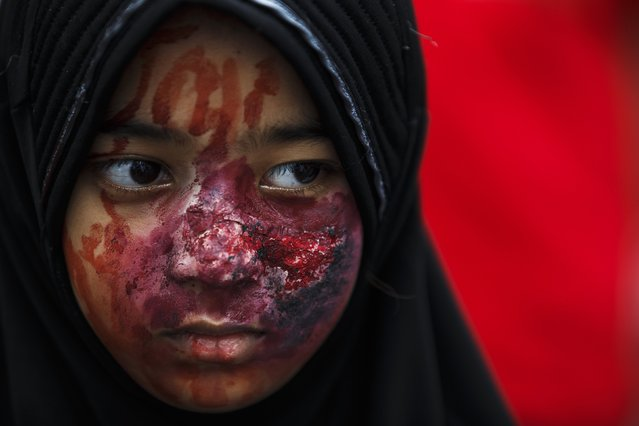 A demonstrator wears make-up of injuries during an anti-Israel protest, in front of the Israeli embassy, in Bangkok July 25, 2014. Gazan authorities said Israeli forces shelled a shelter at a U.N.-run school on Thursday, killing at least 15 people as the Palestinian death toll in the conflict climbed over 760 and attempts at a truce remained elusive. The Israeli military said it was investigating the incident. (Photo by Athit Perawongmetha/Reuters)