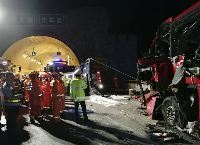 In this photo released by China's Xinhua News Agency, first responders work at the site of an accident after a coach hit the wall of the Qinling Mountains No. 1 Tunnel on the Jingkun Expressway in Ningshan County, northwestern China's Shaanxi Province, Friday, August 11, 2017. The passenger coach crashed into the wall of the expressway tunnel in China's northwest, killing dozens and injuring others, official media reported Friday. (Photo by Xinhua via AP Photo)