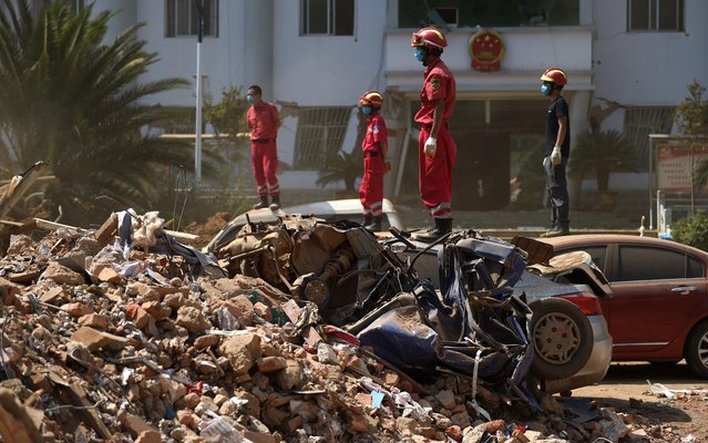 Rescue crew members watch as machinery is used to dig through the rubble of collapsed houses at Longtoushan, in China's southwest Yunnan province on August 7, 2014. The death toll from an earthquake that devastated a remote region of China jumped to nearly 600 people on August 6, authorities said, as volunteer rescuers were warned away. (Photo by Greg Baker/AFP Photo)
