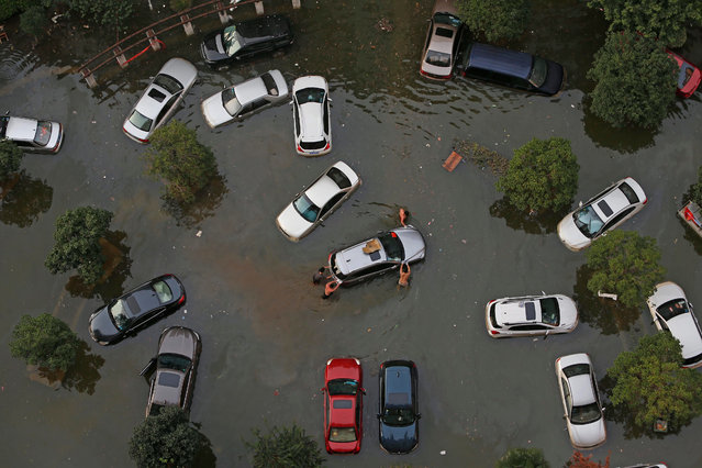 A picture made available on 10 July 2016 shows people pushing a car after flood waters receded to reveal the submerged vehicles in Wuhan, Hubei Province, China, 09 July 2016. (Photo by Yuan Zheng/EPA)