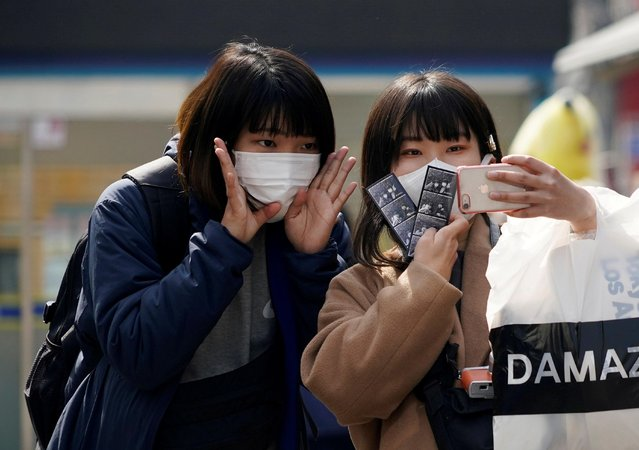 Tourists wearing masks to prevent the coronavirus take a selfie at a shopping district in Seoul, South Korea, February 24, 2020. (Photo by Kim Hong-Ji/Reuters)