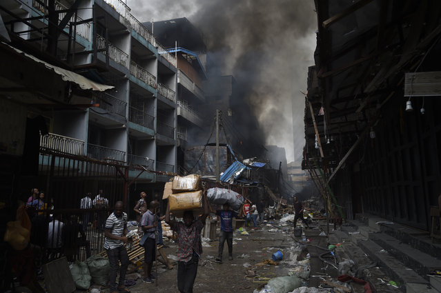 People carry goods salvaged from a fire that broke out in a section of the Balogun market in Lagos on January 29, 2020. More than five high-rise buildings consisting of shops, offices and warehouses, stockpiled with goods, were destroyed in a fire outbreak, the second fire that happened in three months at the Balogun Market in Lagos. (Photo by Pius Utomi Ekpei/AFP Photo)