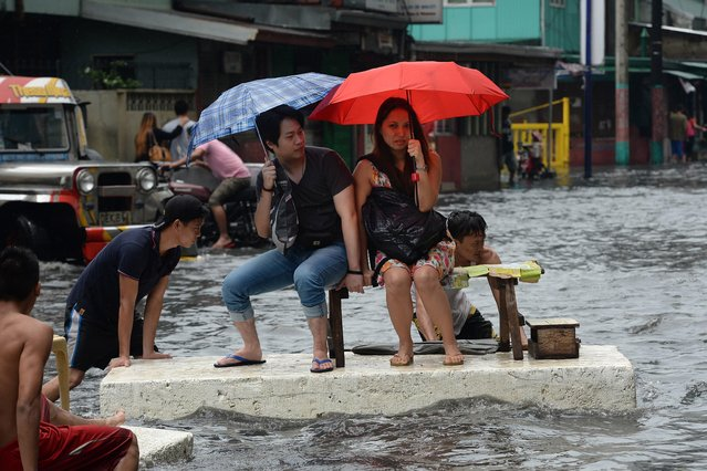 Office workers ride on a makeshift raft made of styrofoam after a sudden heavy downpour inundated streets in the financial district of Manila on August 12, 2015, stranding thousands of commuters and office workers, with the weather bureau saying the downpour was caused by thunderstorm. (Photo by Ted Aljibe/AFP Photo)