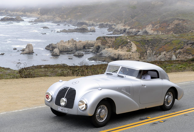 A 1938 Mercedes-Benz 540k Streamliner, from the Mercedes-Benz classic collection, rolls past Sobranes Point in Big Sur, Calif., Thursday, August 14, 2014, during the 2014 Pebble Beach Tour D'Elegance. During the event vehicles traveled from Pebble Beach to Laguna Seca Raceway, down the coast to Big Sur and back to Carmel. (Photo by David Royal/AP Photo/Monterey Herald)