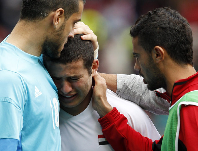 Goalkeeper Mohamed Bassam (L) of Egypt comforts team mate Eslam Ramadan (C) as he cries after their men's quarterfinal soccer match against Japan at the London 2012 Olympic Games at Old Trafford in Manchester, August 4, 2012. (Photo by Andrea Comas/Reuters)