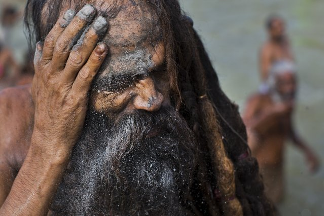 An Indian Sadhu, or Hindu holy man, rubs ash on his face after a bath in the Godavari River during Kumbh Mela, or Pitcher Festival, in Nasik, India, Saturday, August 29, 2015. (Photo by Bernat Armangue/AP Photo)