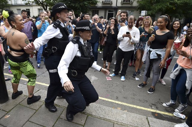 Revellers watch as police officers dance in the street at the Notting Hill Carnival in west London, August 30, 2015. (Photo by Toby Melville/Reuters)