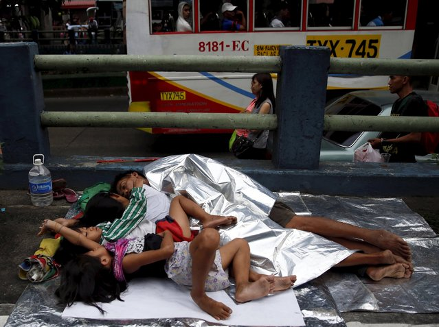 A family belonging to the religious group Iglesia ni Cristo (Church of Christ) sleeps on the pavement along the main highway EDSA in Mandaluyong, Metro Manila August 31, 2015. Traffic came to almost a halt at a busy intersection of Manila's main highway on Sunday as thousands of members of a Christian group occupied the road for a third night in a row to protest alleged intrusion by the government in church affairs. (Photo by Erik De Castro/Reuters)