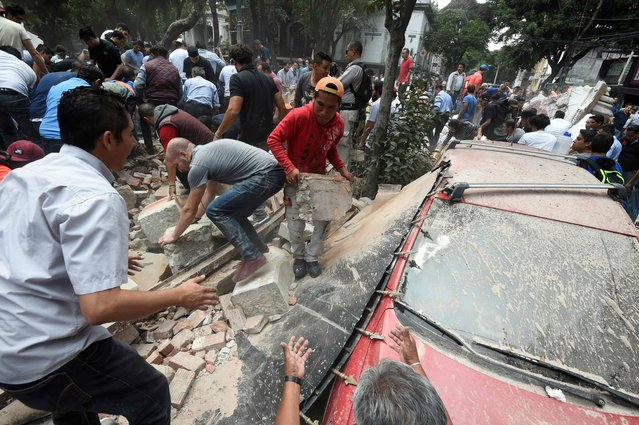 People remove debris of a building which collapsed after a quake rattled Mexico City on September 19, 2017. (Photo by Alfredo Estrella/AFP Photo)